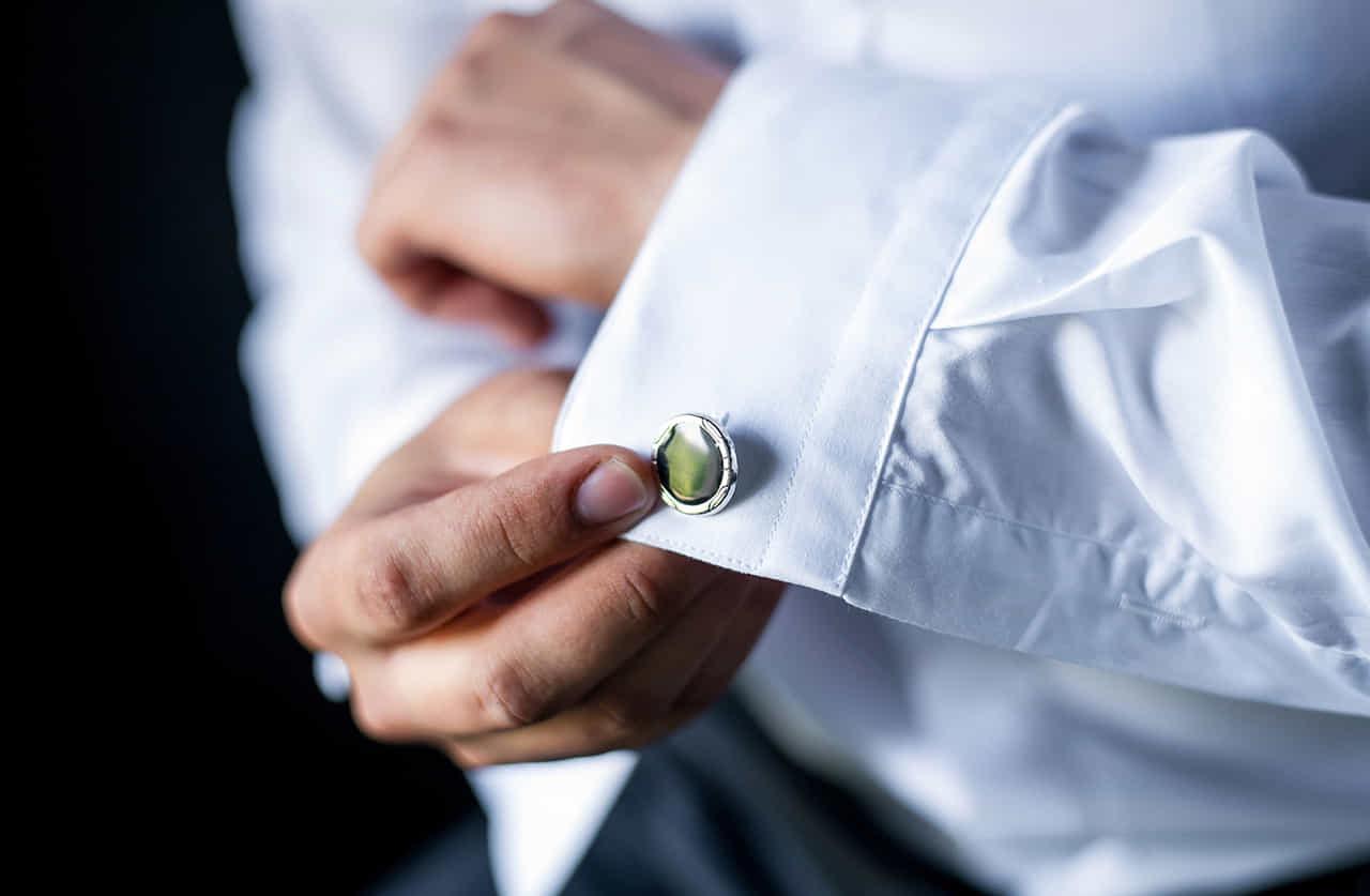 白いシャツを身につけカフスボタンをつける男性