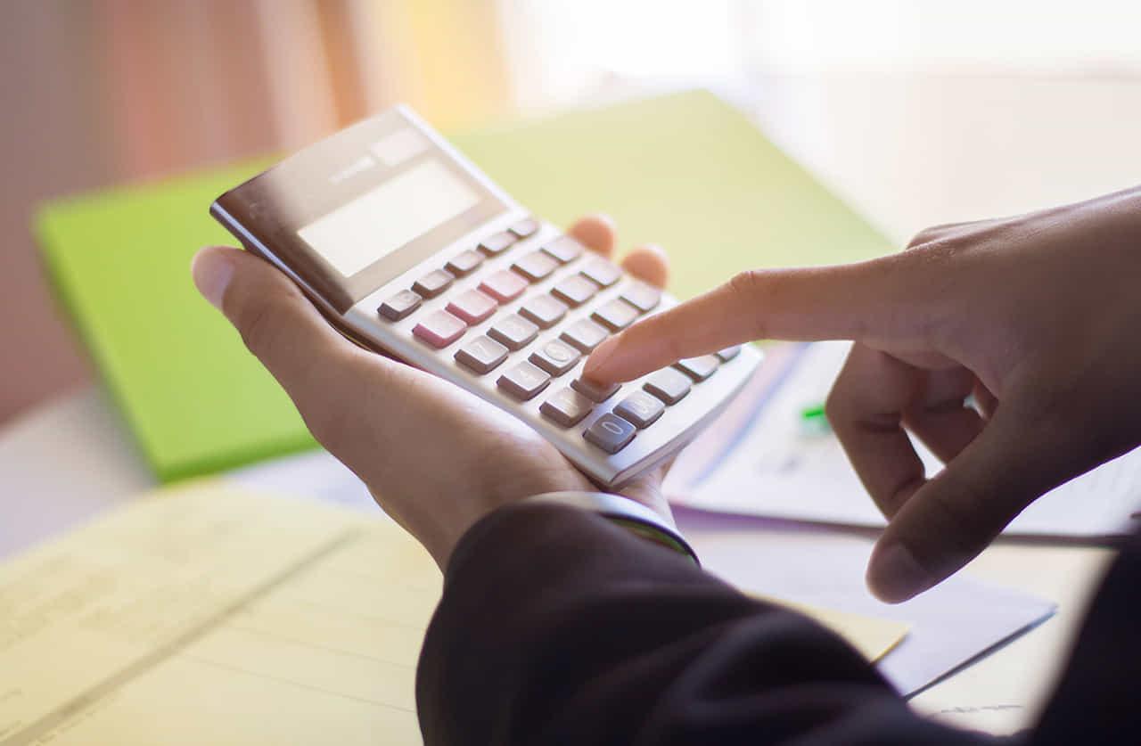 書類を広げたデスクの上で電卓をはじいて計算する背広の男の手