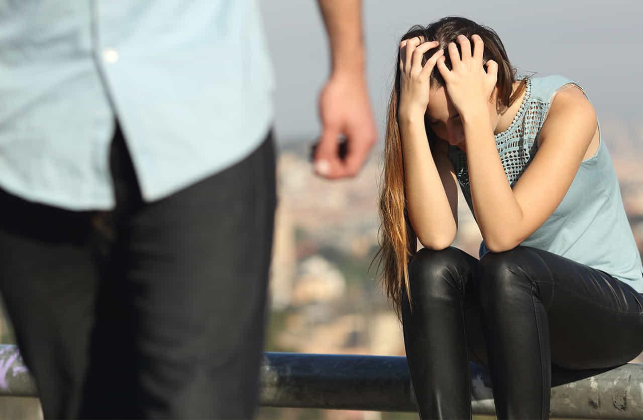 両手で頭を抱え、悲しみに暮れる女性を背に立ち去る男性