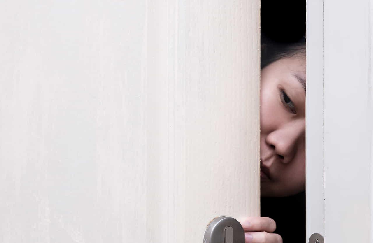 ドアの隙間から覗き見する女性