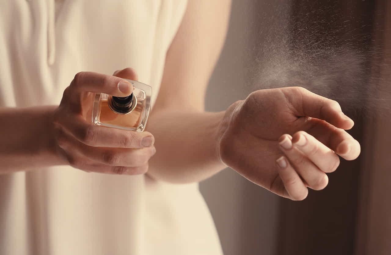 白いブラウスの女性が手首に香水を吹きかけている