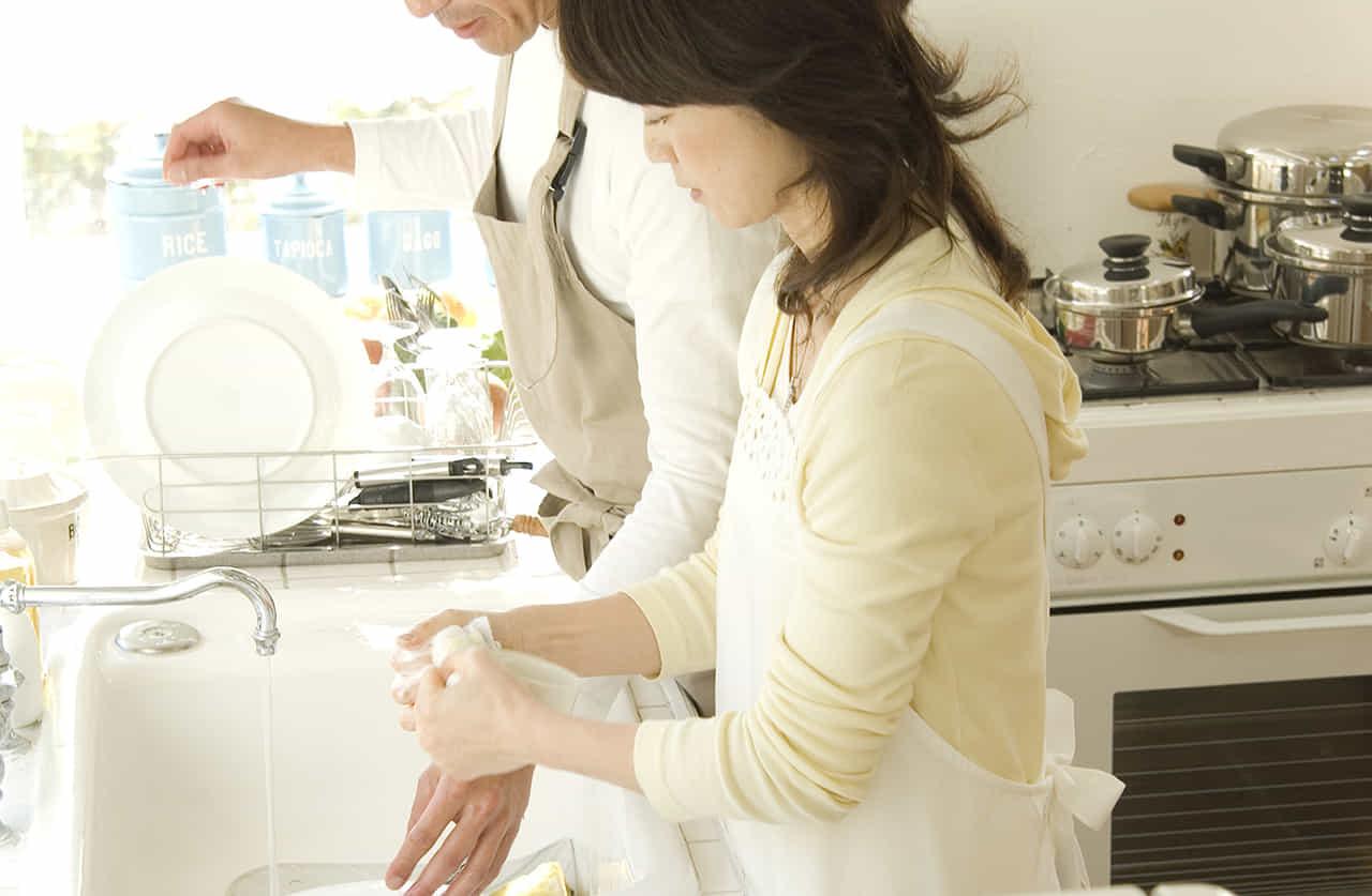 キッチで妻の皿洗いを手伝うエプロン姿の中年男性