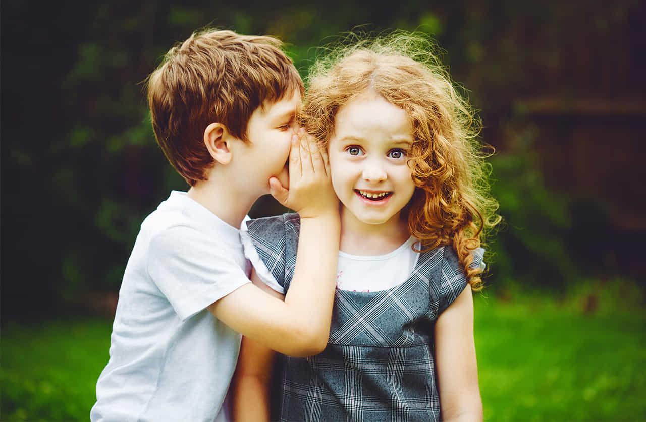 男の子が女の子に秘密の話を耳打ちする