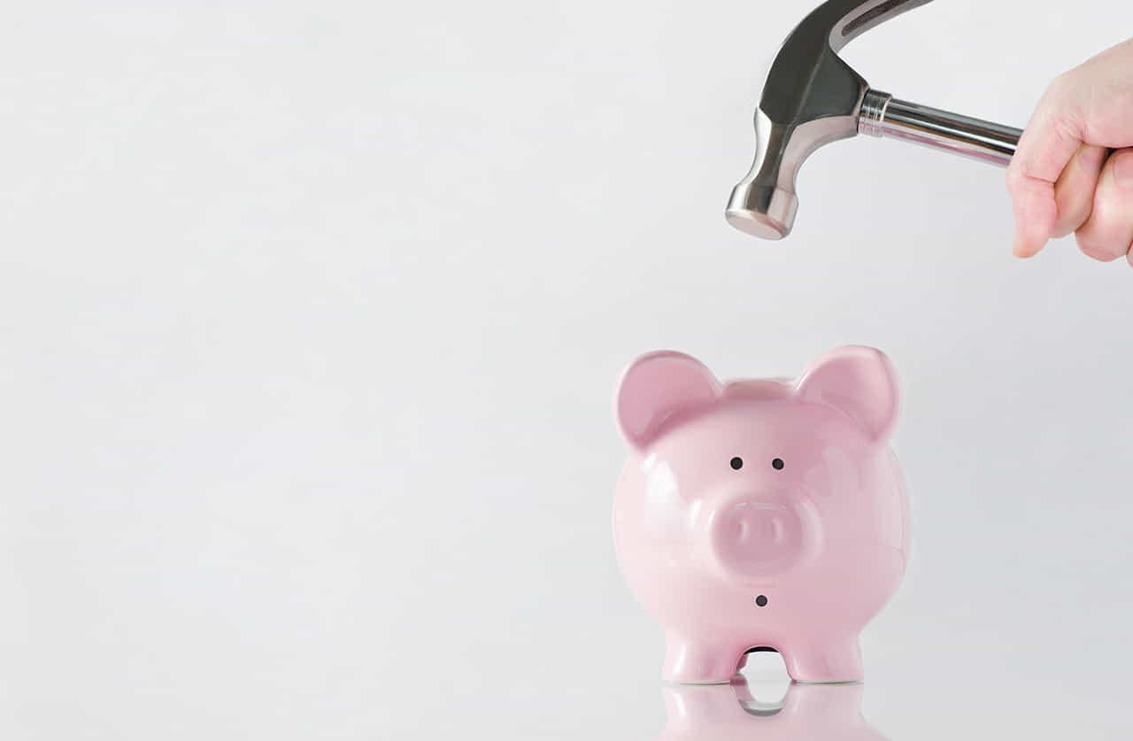豚の貯金箱を割ってお金を取り出そうとしている