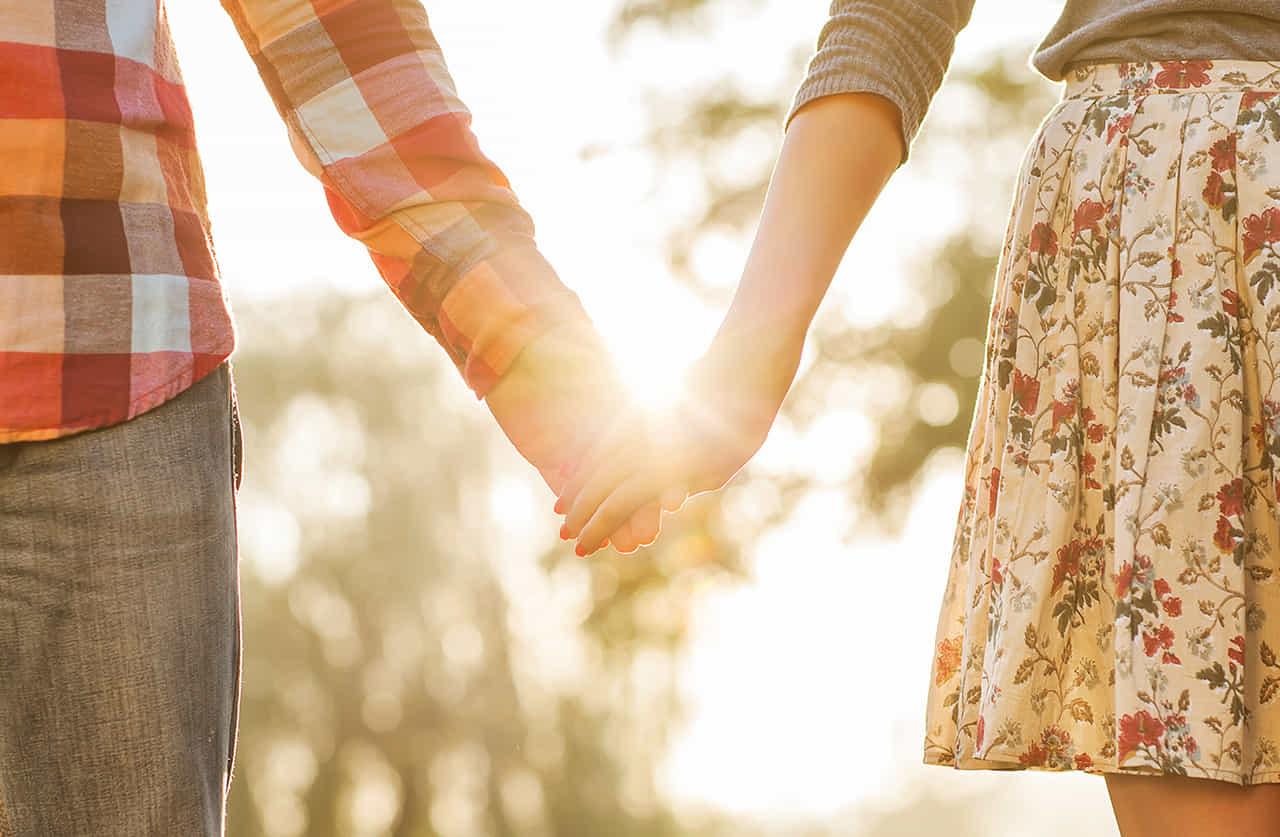 光が溢れる自然の中で手を繋ぐカップル