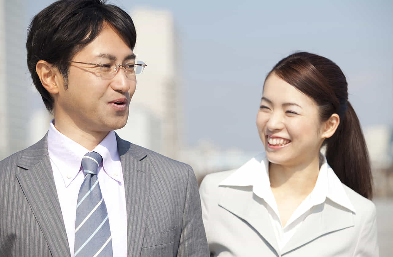 会社の同僚の男女が外回りの営業のため談笑しながら歩いている