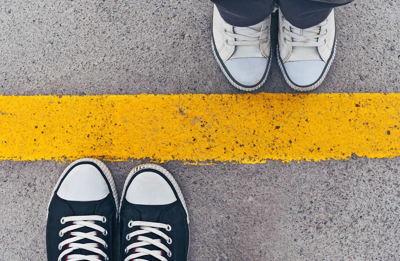黄色い線を挟んで向かい合う男女の足