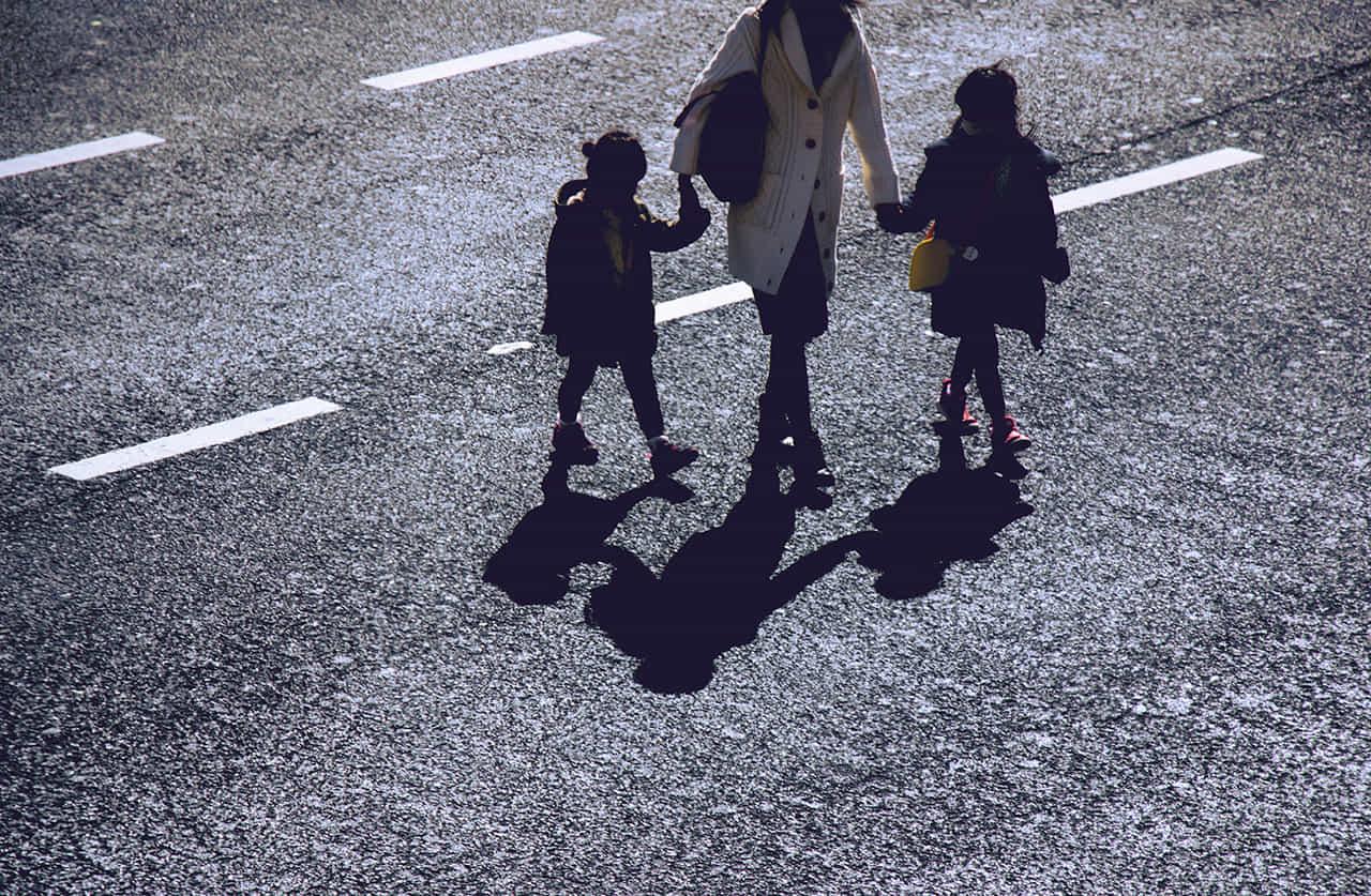 通学させるため子供達の手を引いて歩く主婦