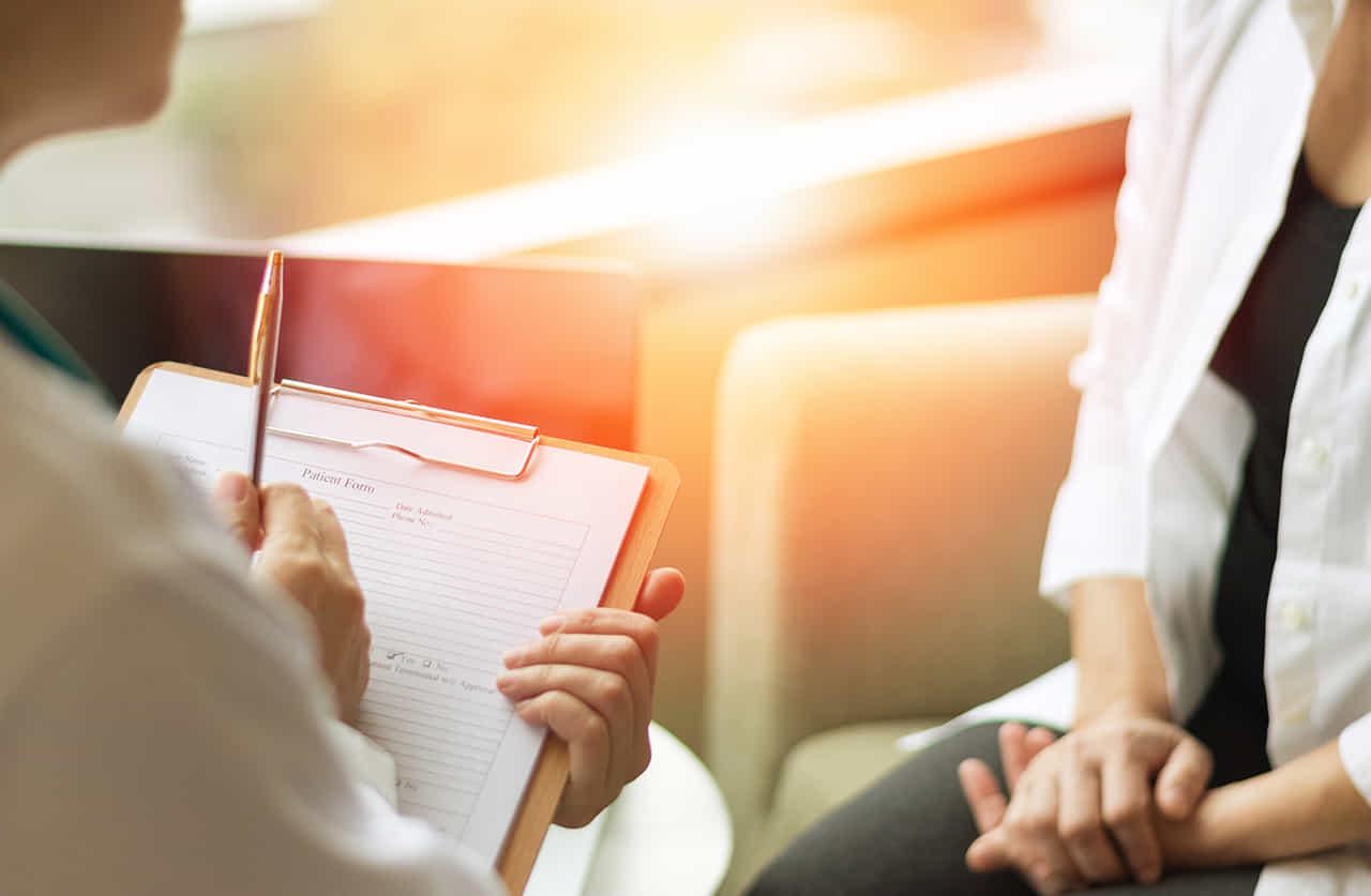 女性患者と対面しカルテに症状を書き込むカウンセラー