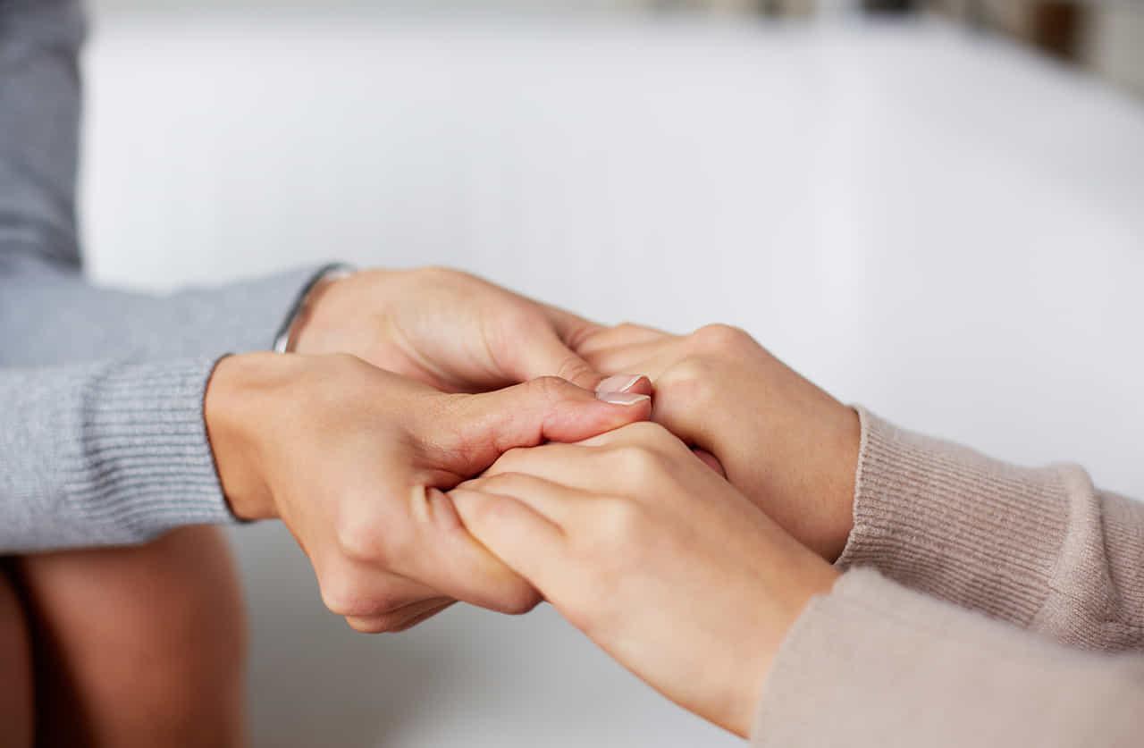 悩んでいる女性をの手を握る女性カウンセラー