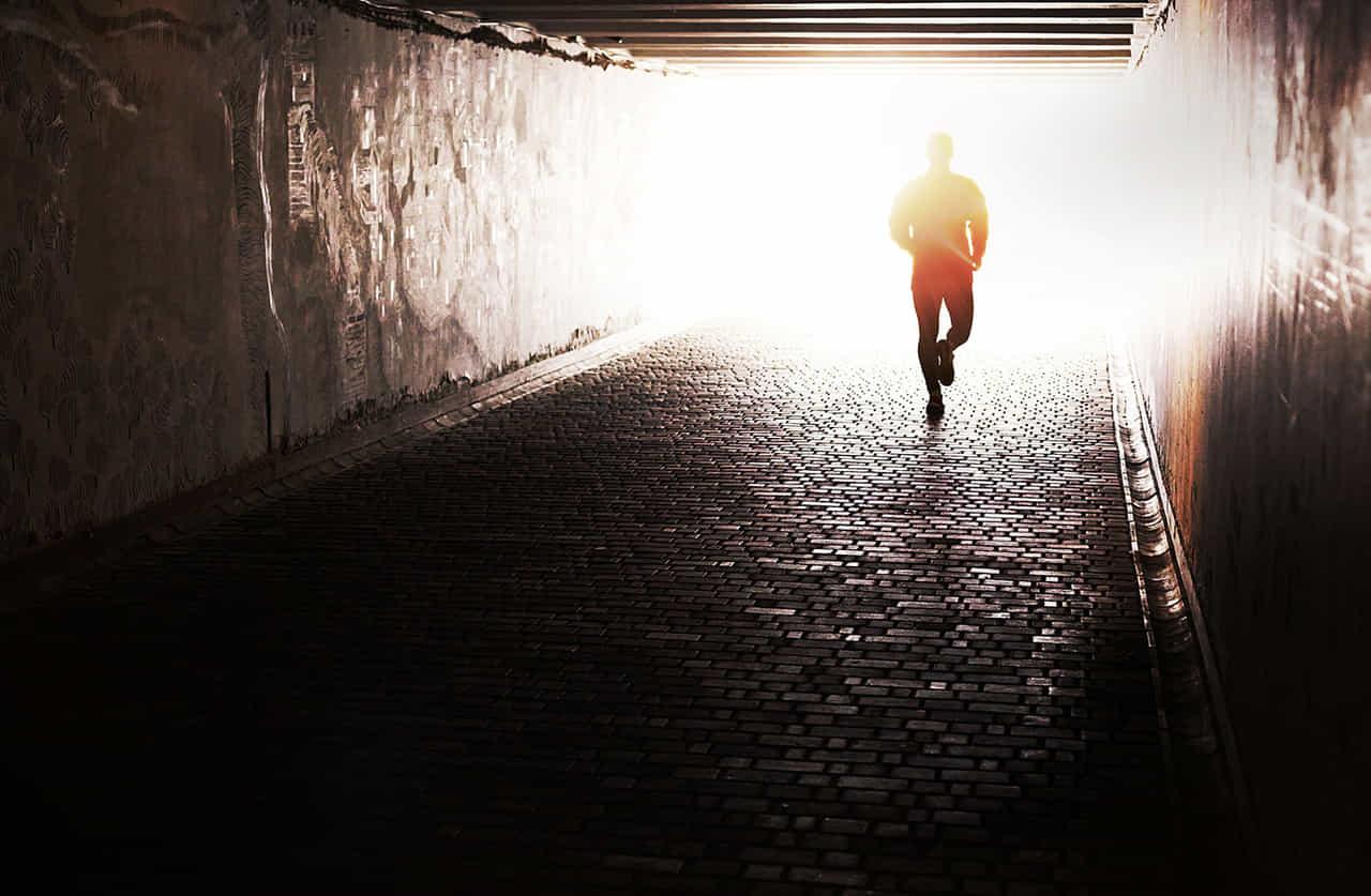 光の射す方へ走っていく男性。現実逃避を揶揄