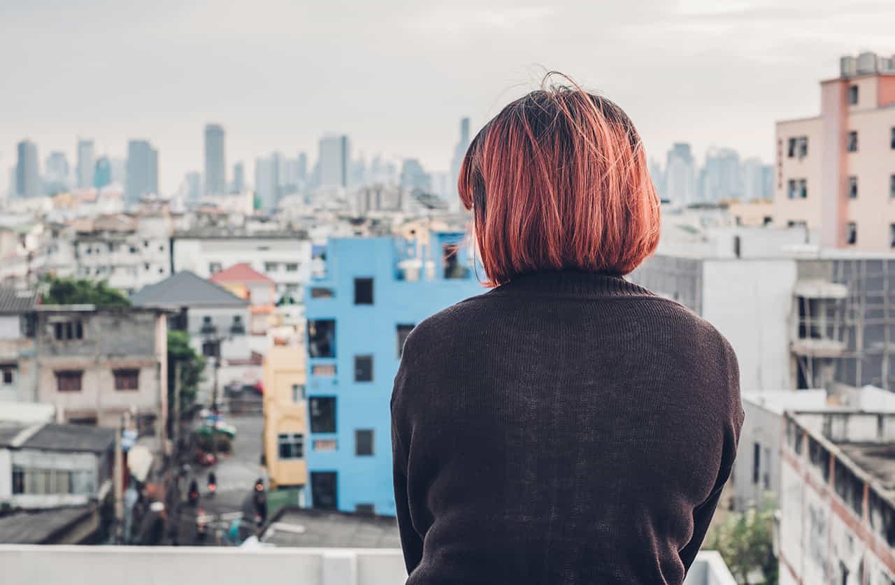 街を見下ろす屋上に佇む女性