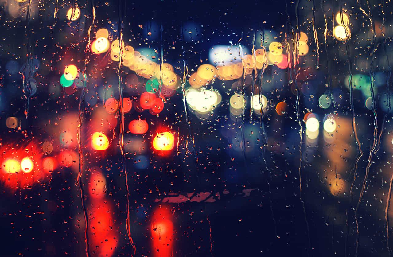 雨に濡れた窓越しに夜の街