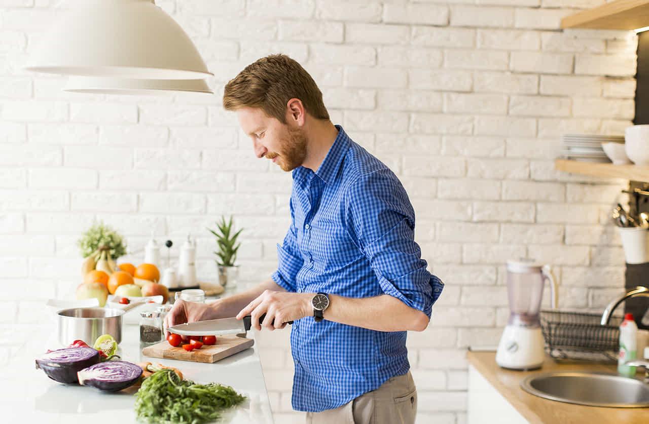 キッチンで楽しそうに料理をする男性