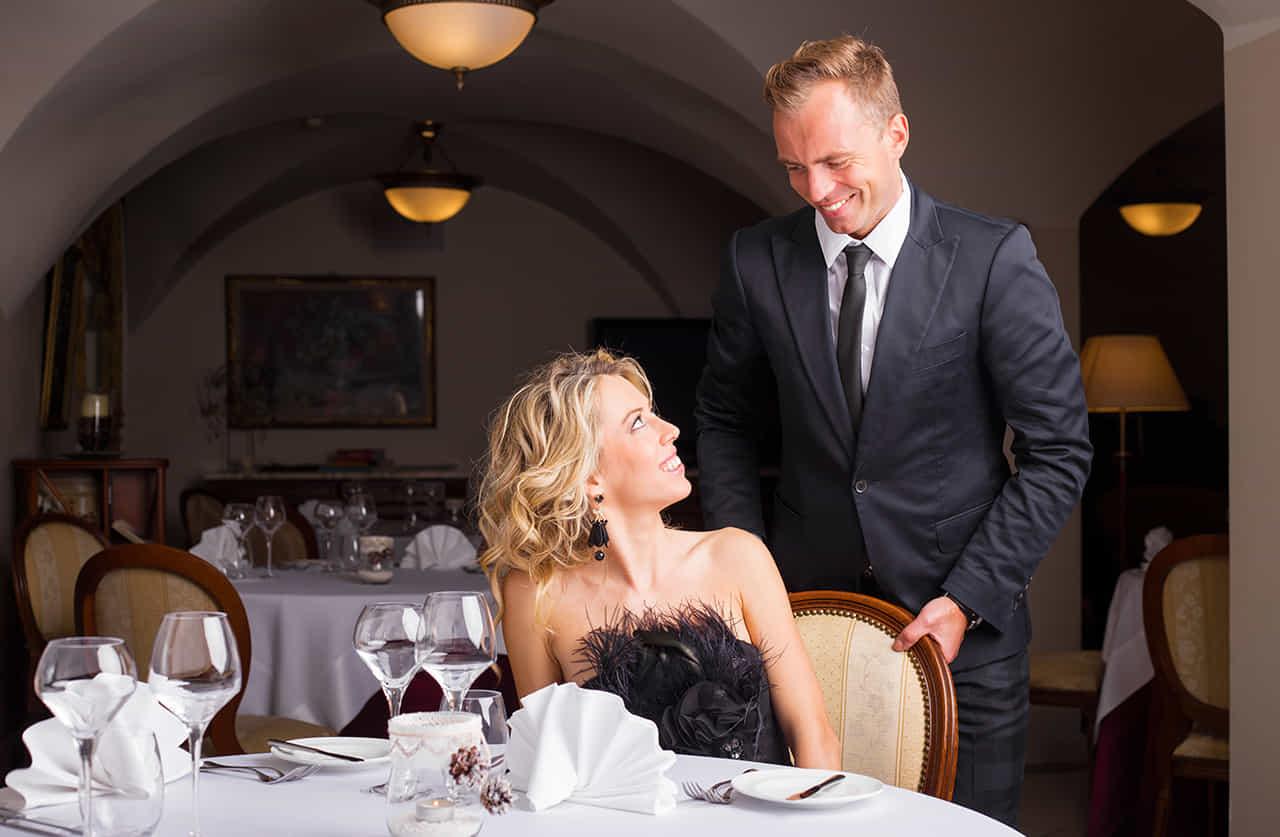 レストランで女性のために椅子を引く紳士