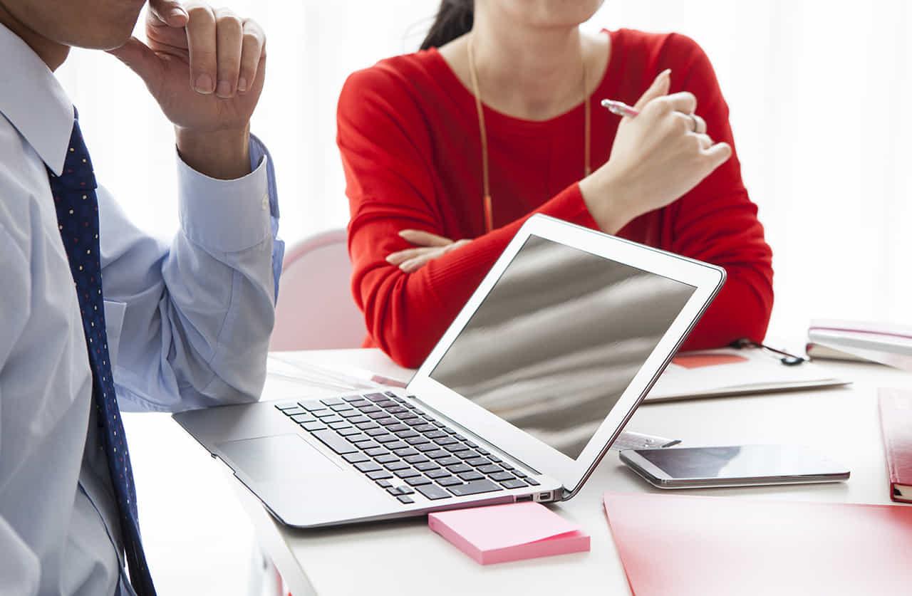 社内の会議室で男性社員と打ち合わせをする赤いセーターの女性