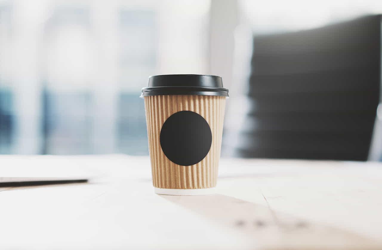 テイクアウトのコーヒーが置いてある朝の会社のデスク