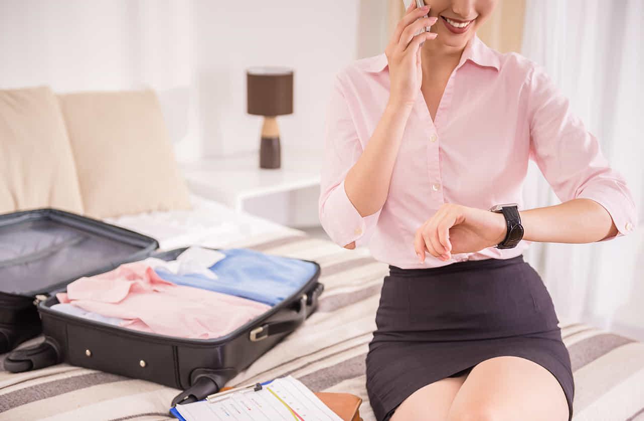ホテルのベッドの上でスーツケースを開き電話する女性