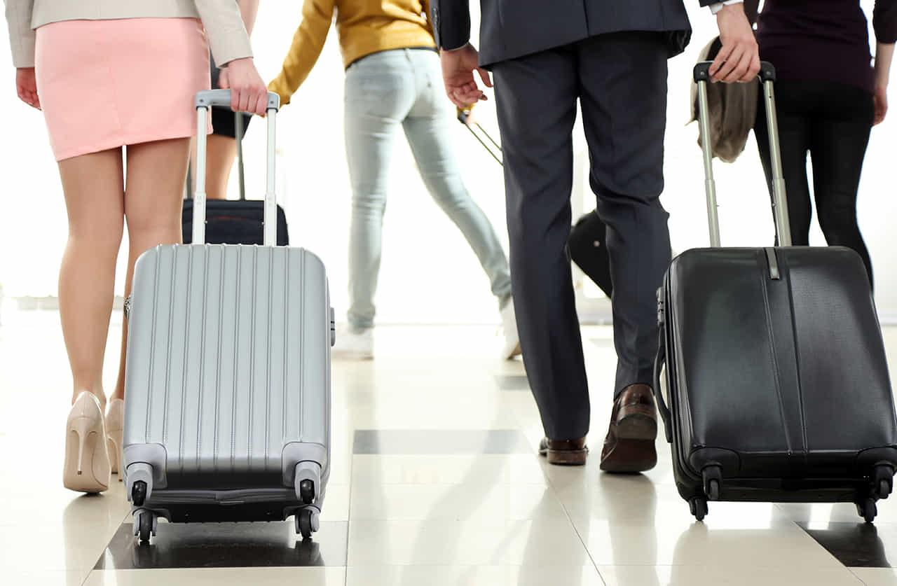 スーツケースを引く男女