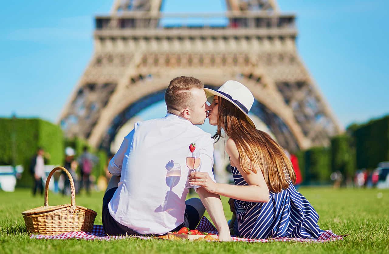パリの公園でピクニックするカップルがキスをしている