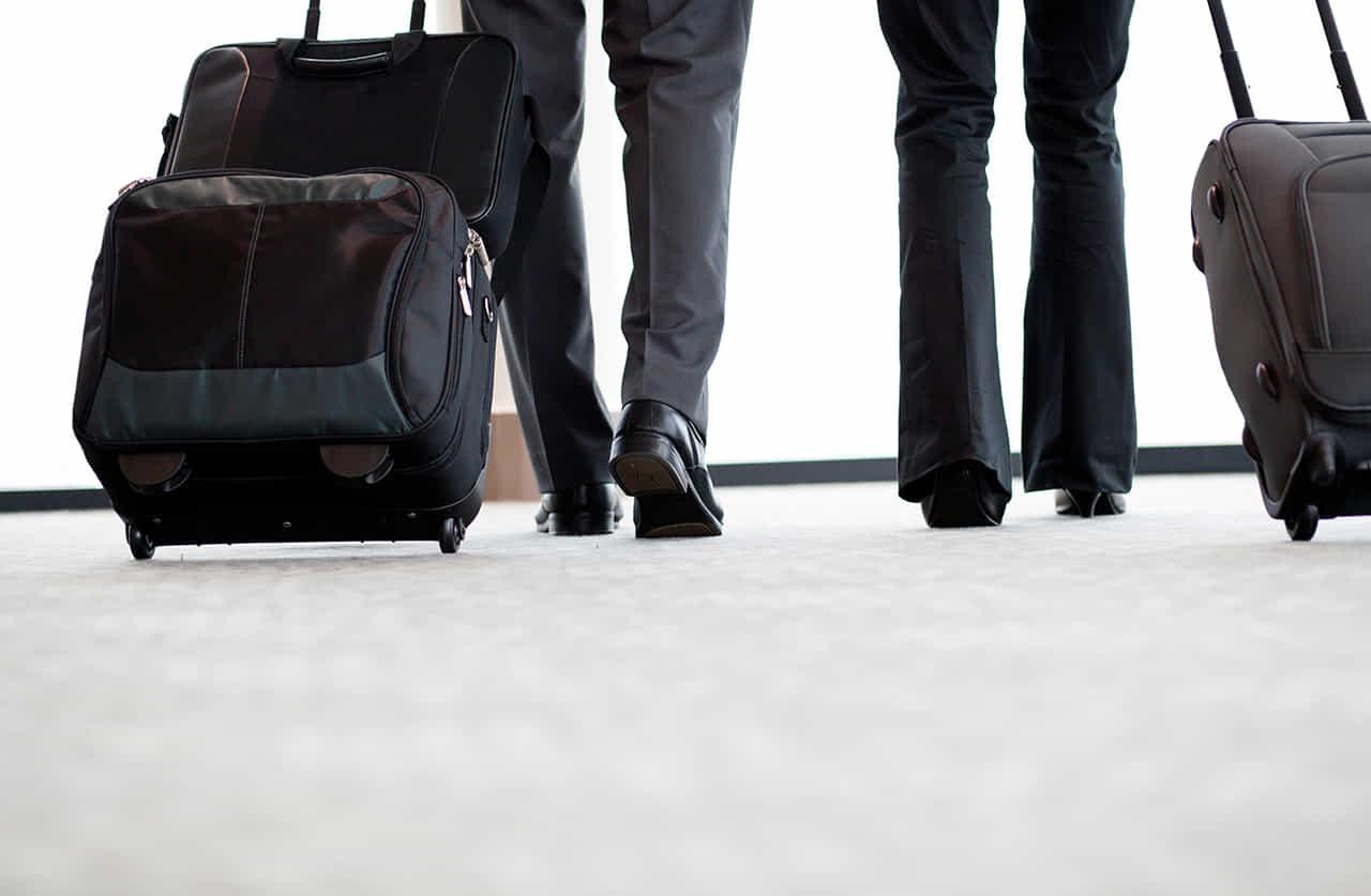 キャリーバッグを引く男女の会社員の足元