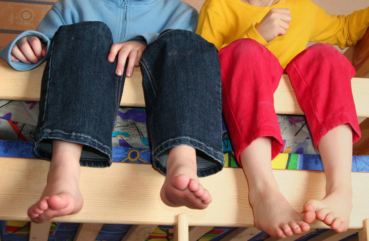 二段ベッドに腰掛ける男女の子供の足