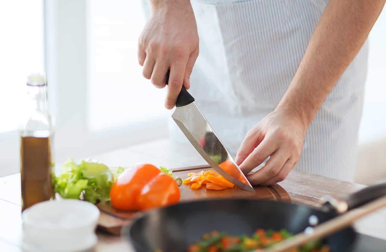 男性が包丁で野菜を切っている手元