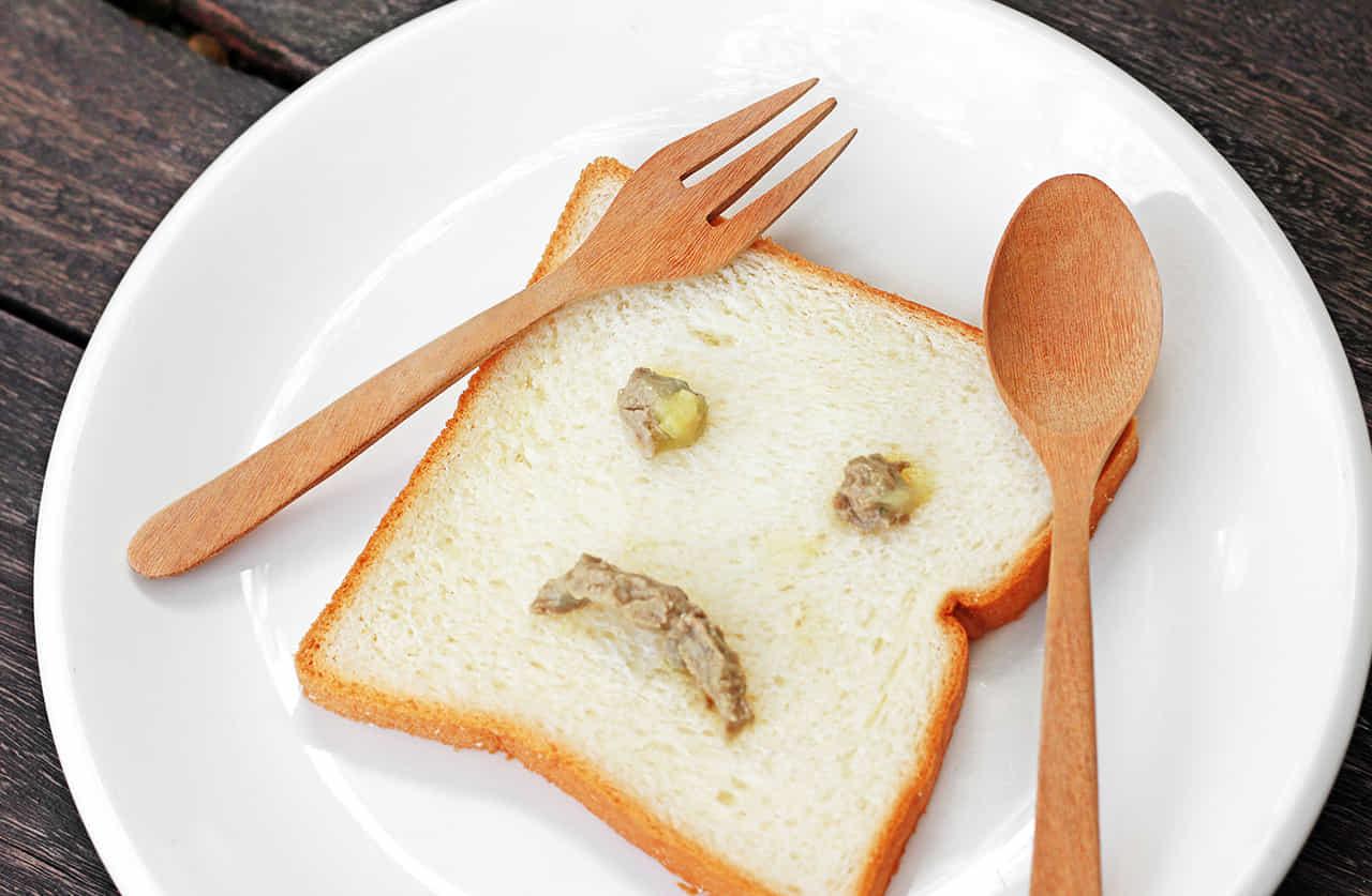 食パンにマスタードで悲しい顔が描かれている