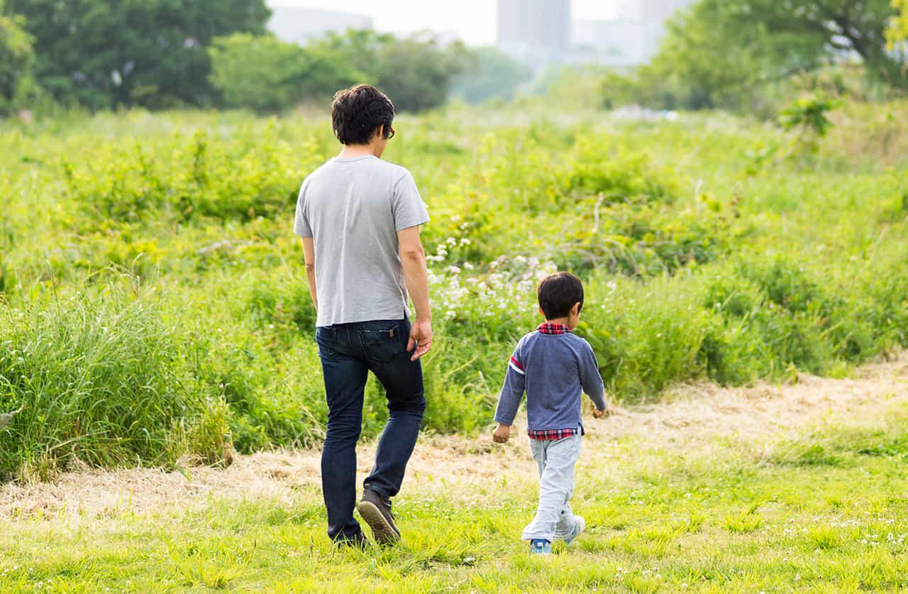 父と息子が土手を歩いている