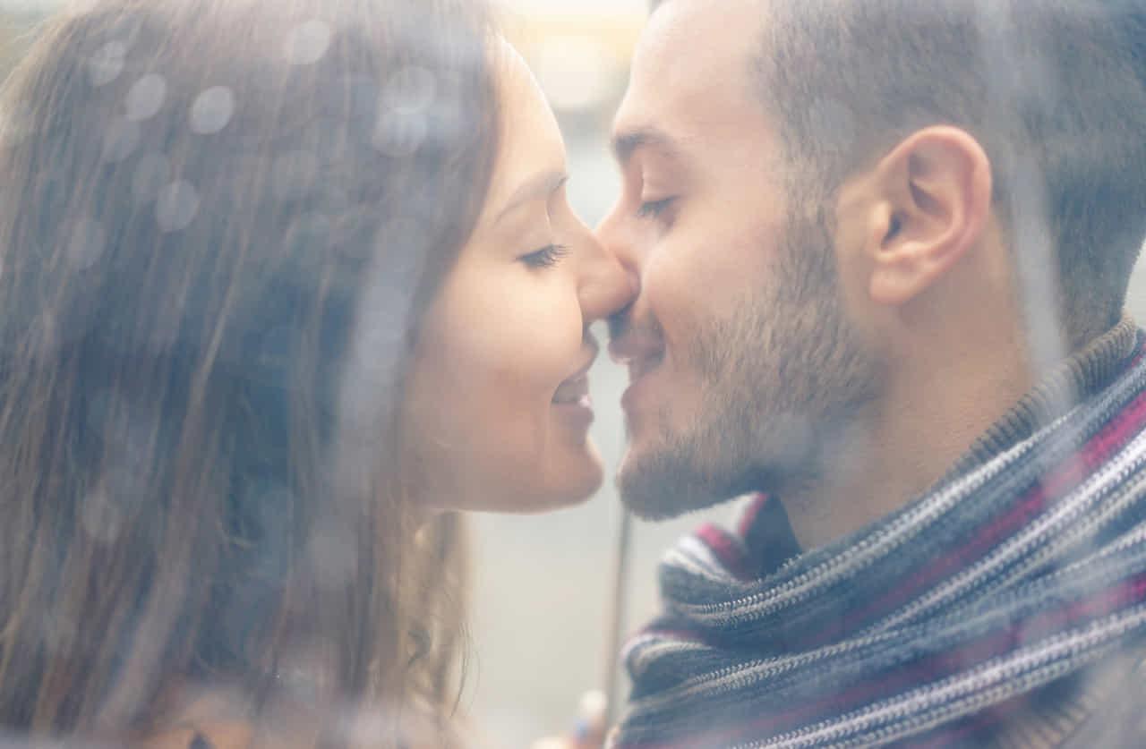 雨の中、傘越しに見えるキスするカップル