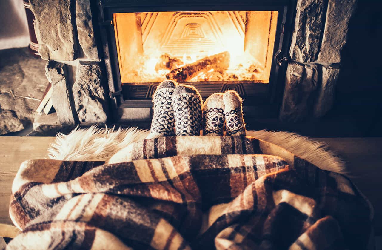 暖炉に足を向ける暖かそうなソックスを履いたカップル