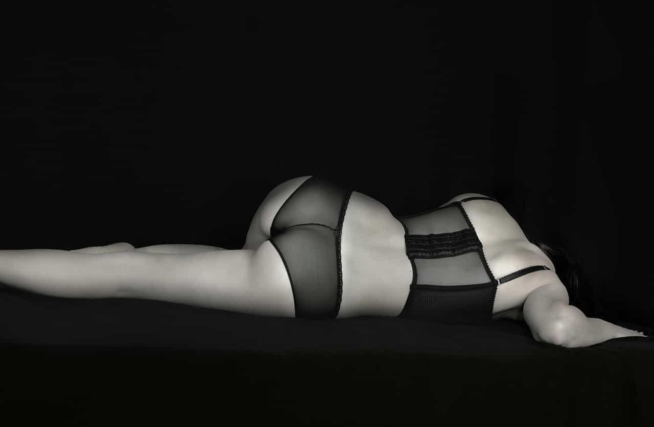 下着姿で横たわる女性のモノクロ写真