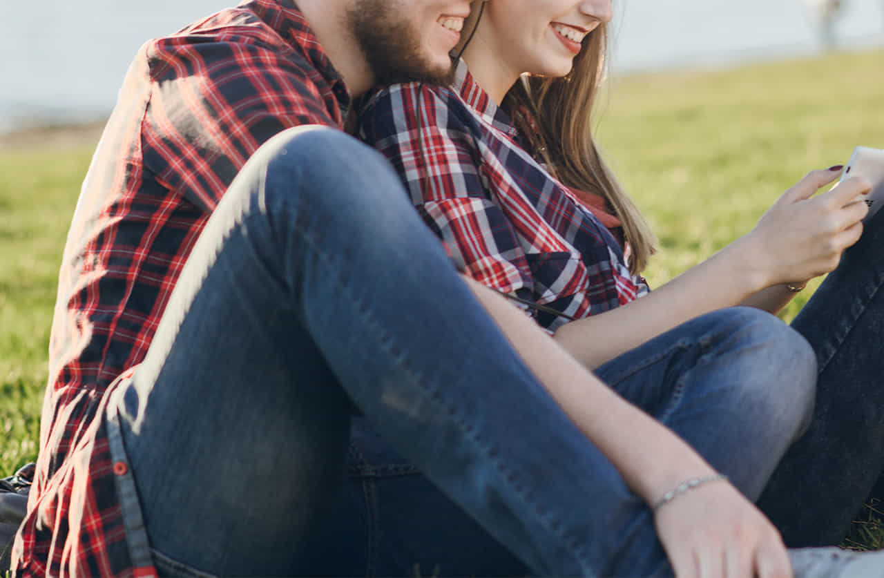 女性に後ろから寄り添って笑っているペアルックのカップル