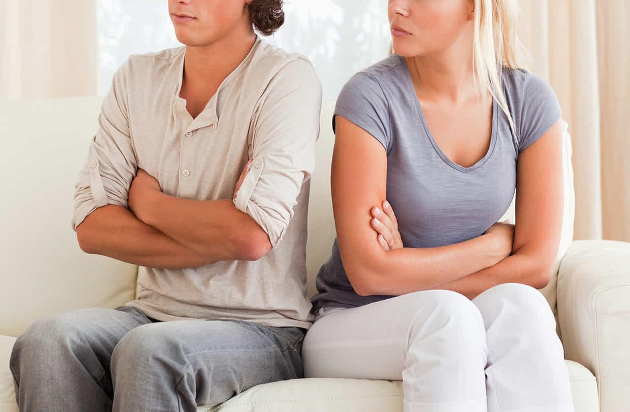 腕を組んで疑いの目で見る女性と腕を組んでそっぽを向く男性