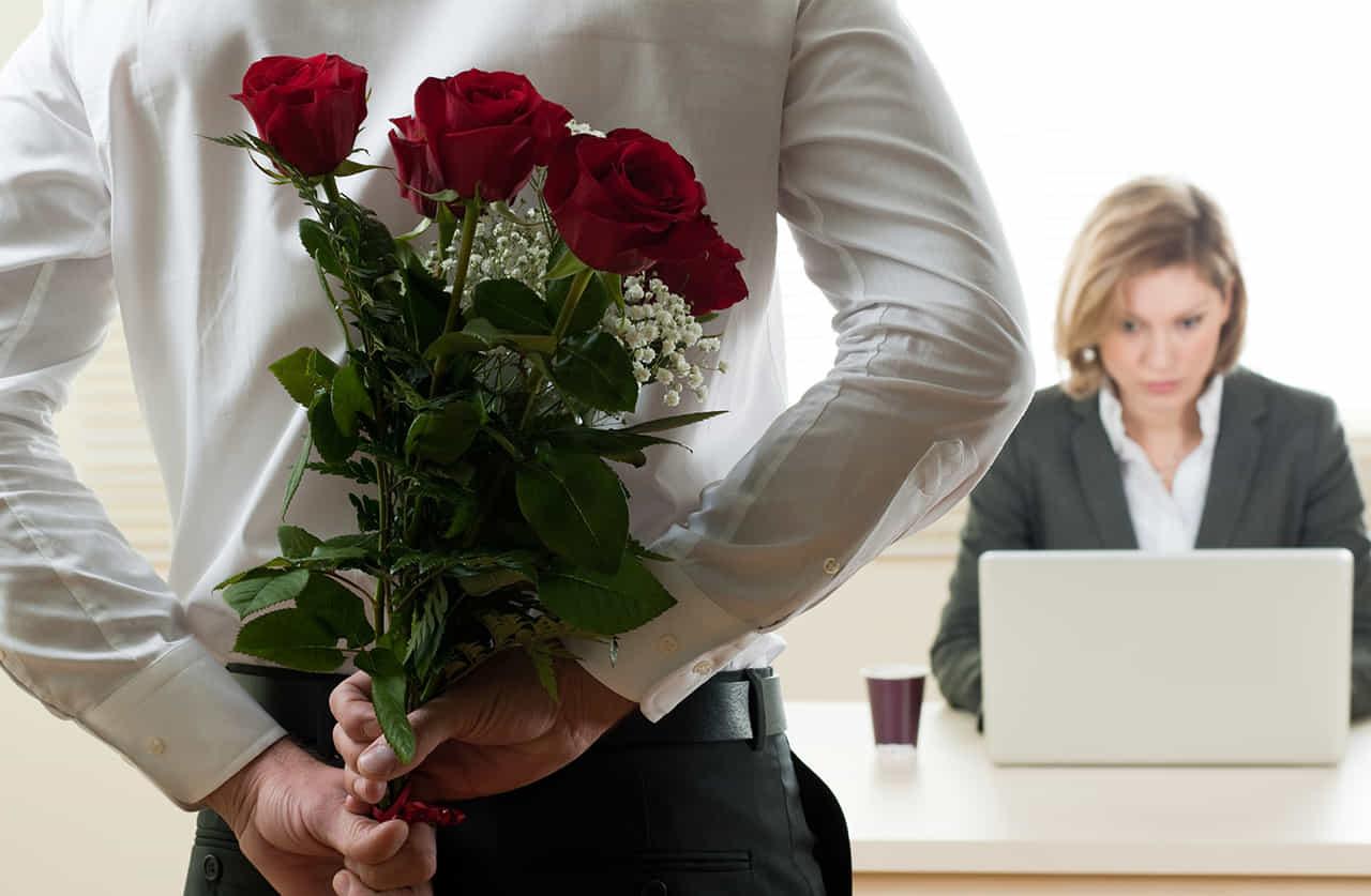 職場内でバラの花束を持って女性にアプローチをしようとしている男性