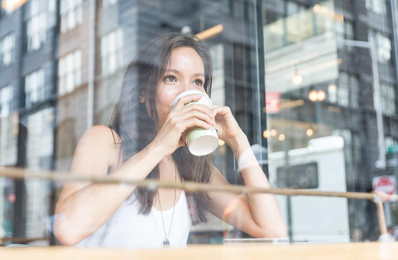カフェの窓際の席で外を見つめ朝のコーヒーを飲む女性