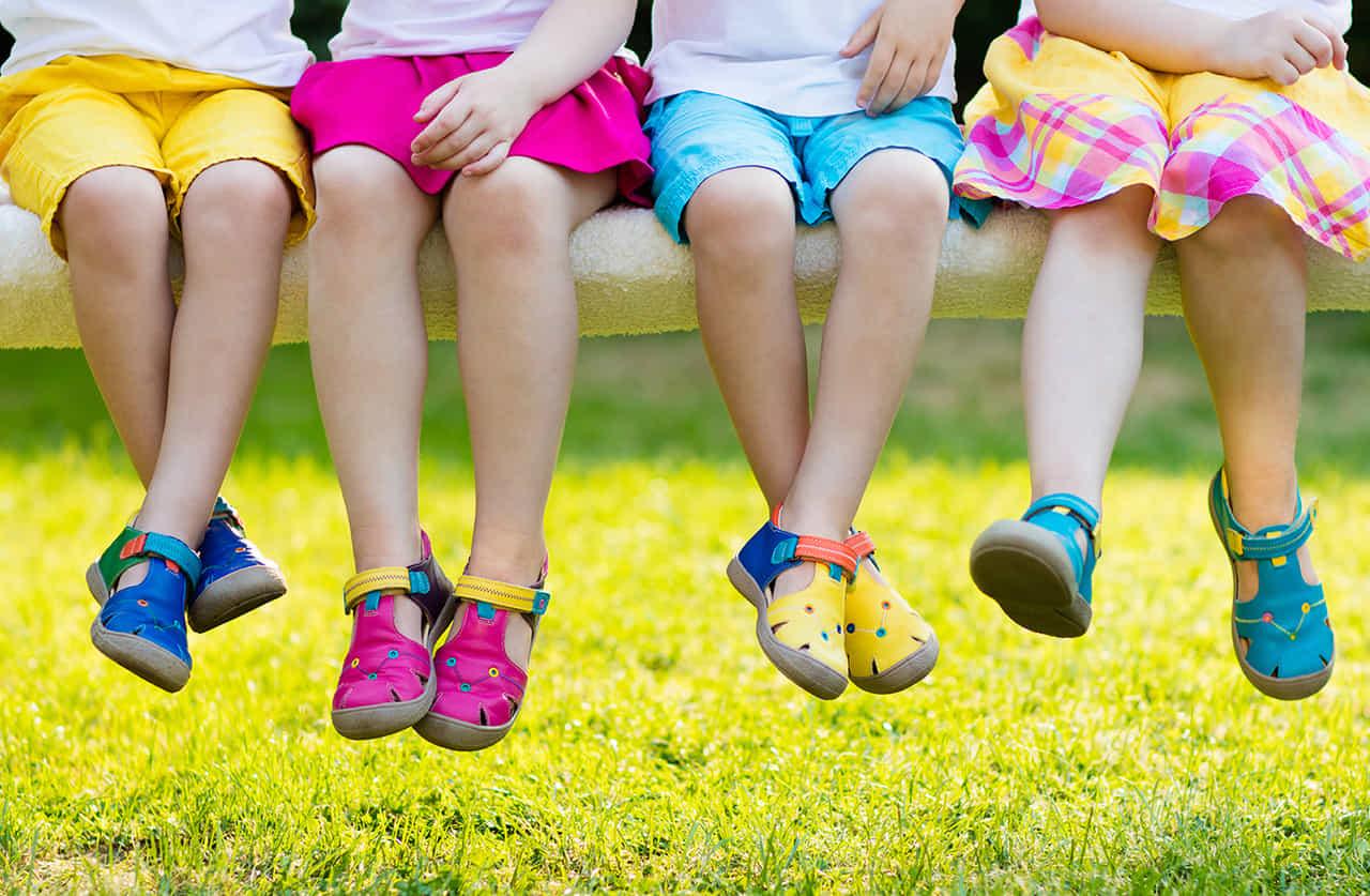 カラフルな洋服を着た4人の幼児の脚