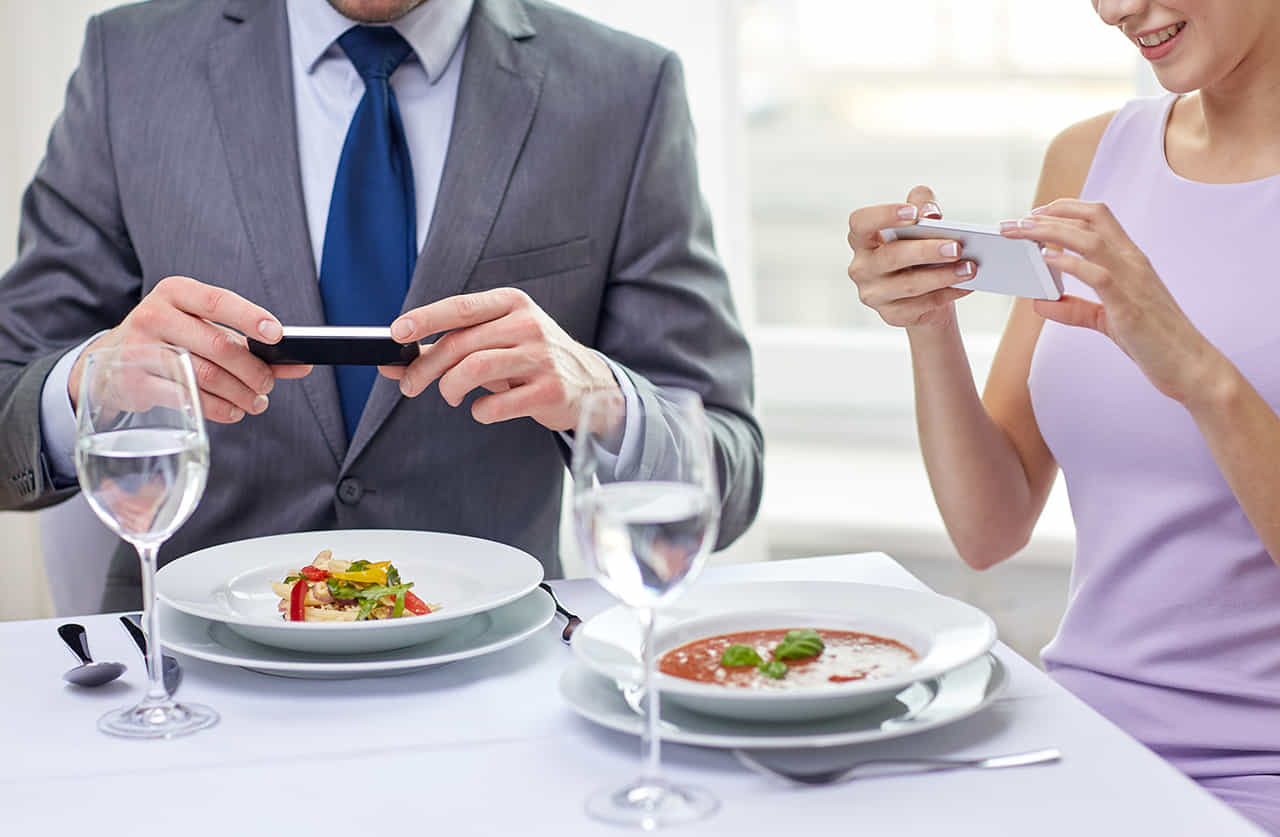レストランのランチで料理をスマホで撮影するカップル