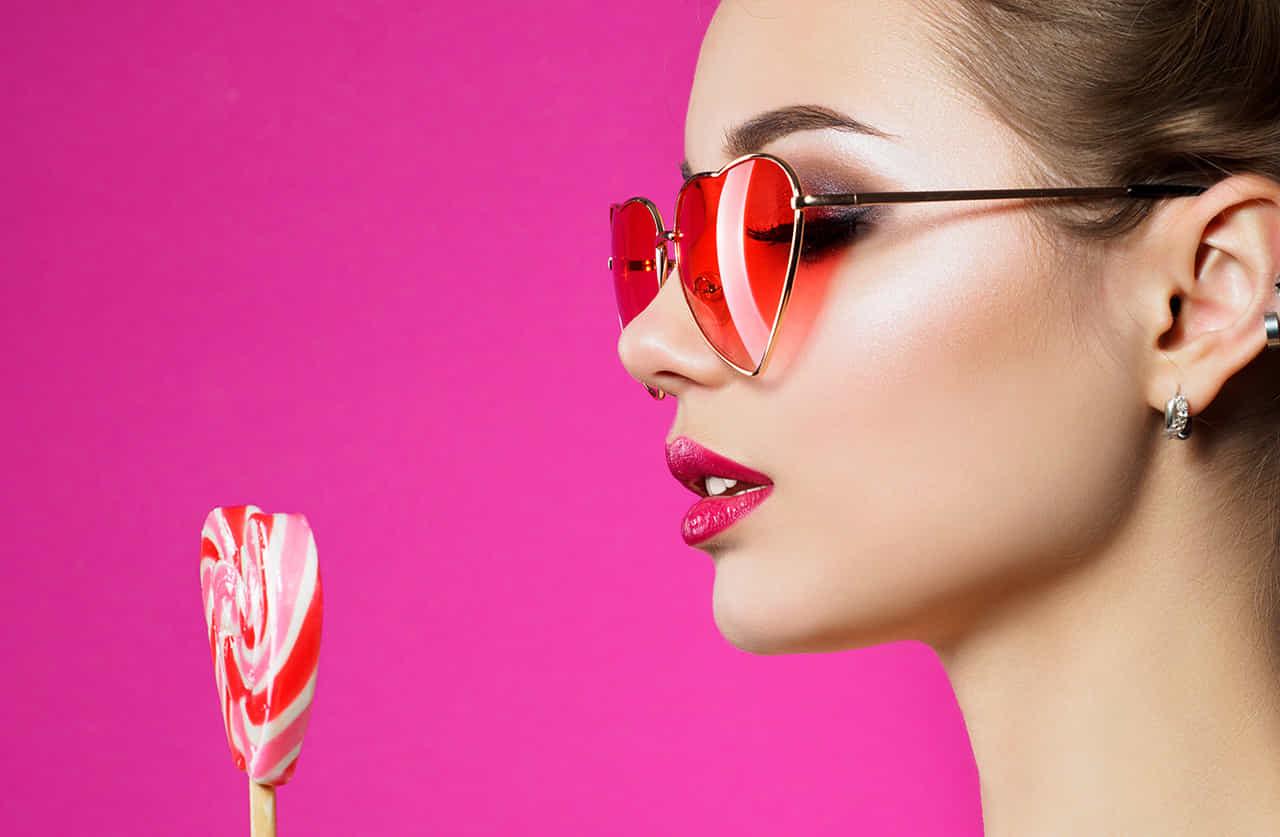 ハートのサングラスをした幼い女性とキャンディー