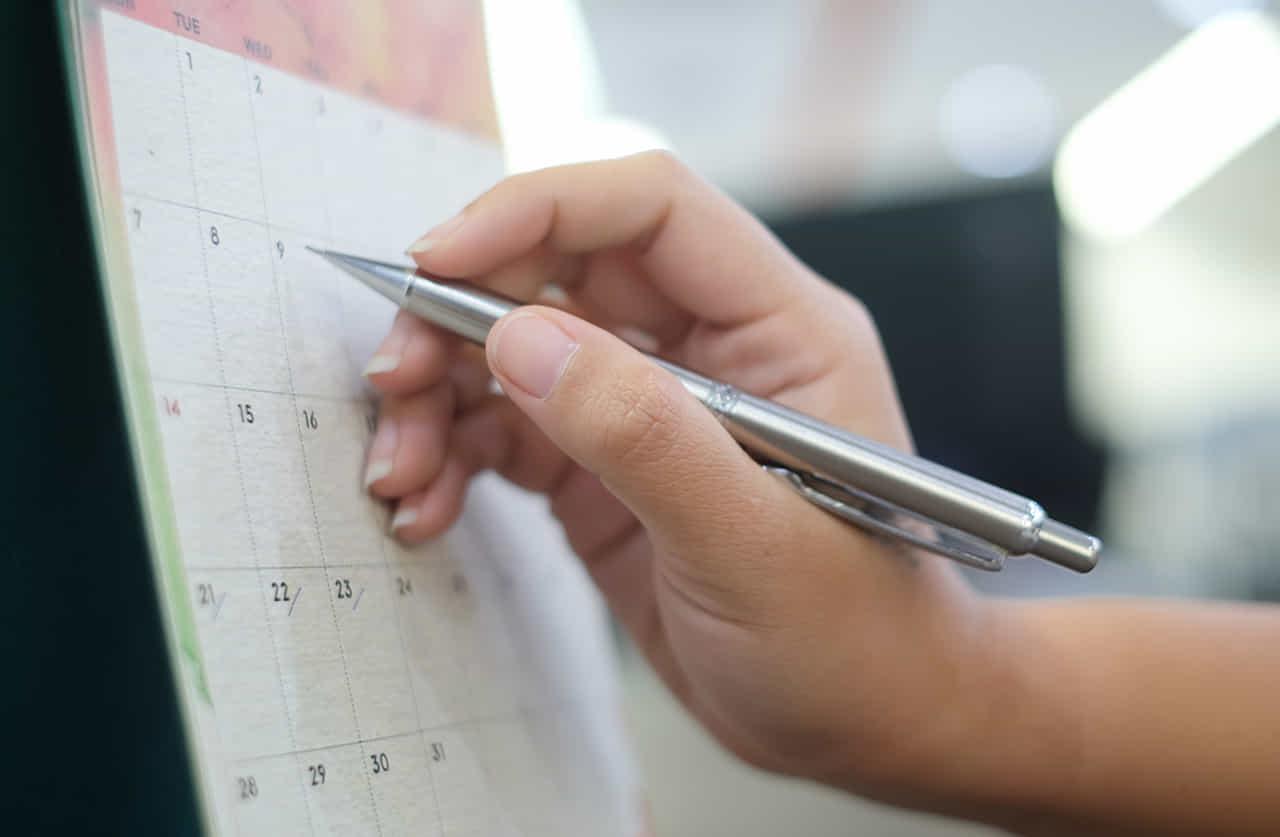 カレンダーに予定を書き入れる女性