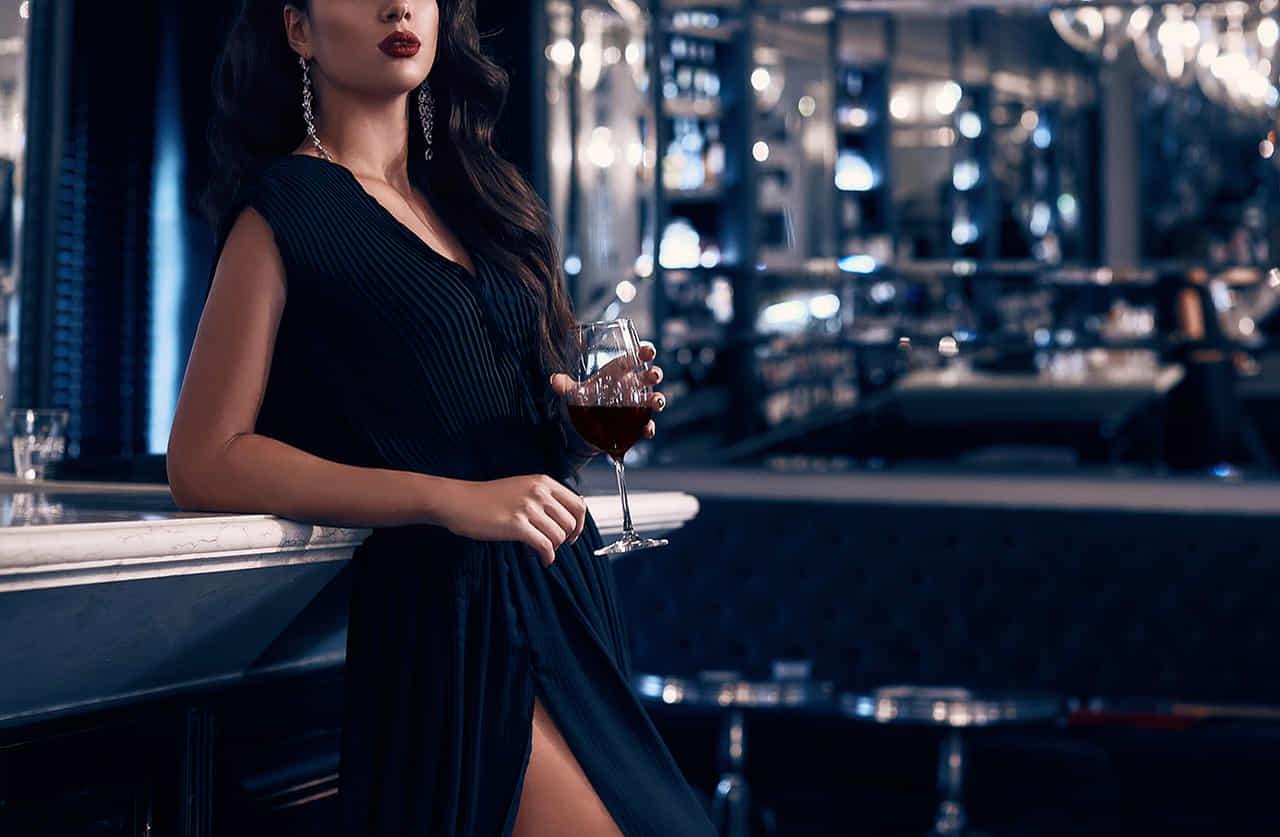 黒い脚に大きくスリットが入ったドレスを着てお店のカウンターにもたれるホステス