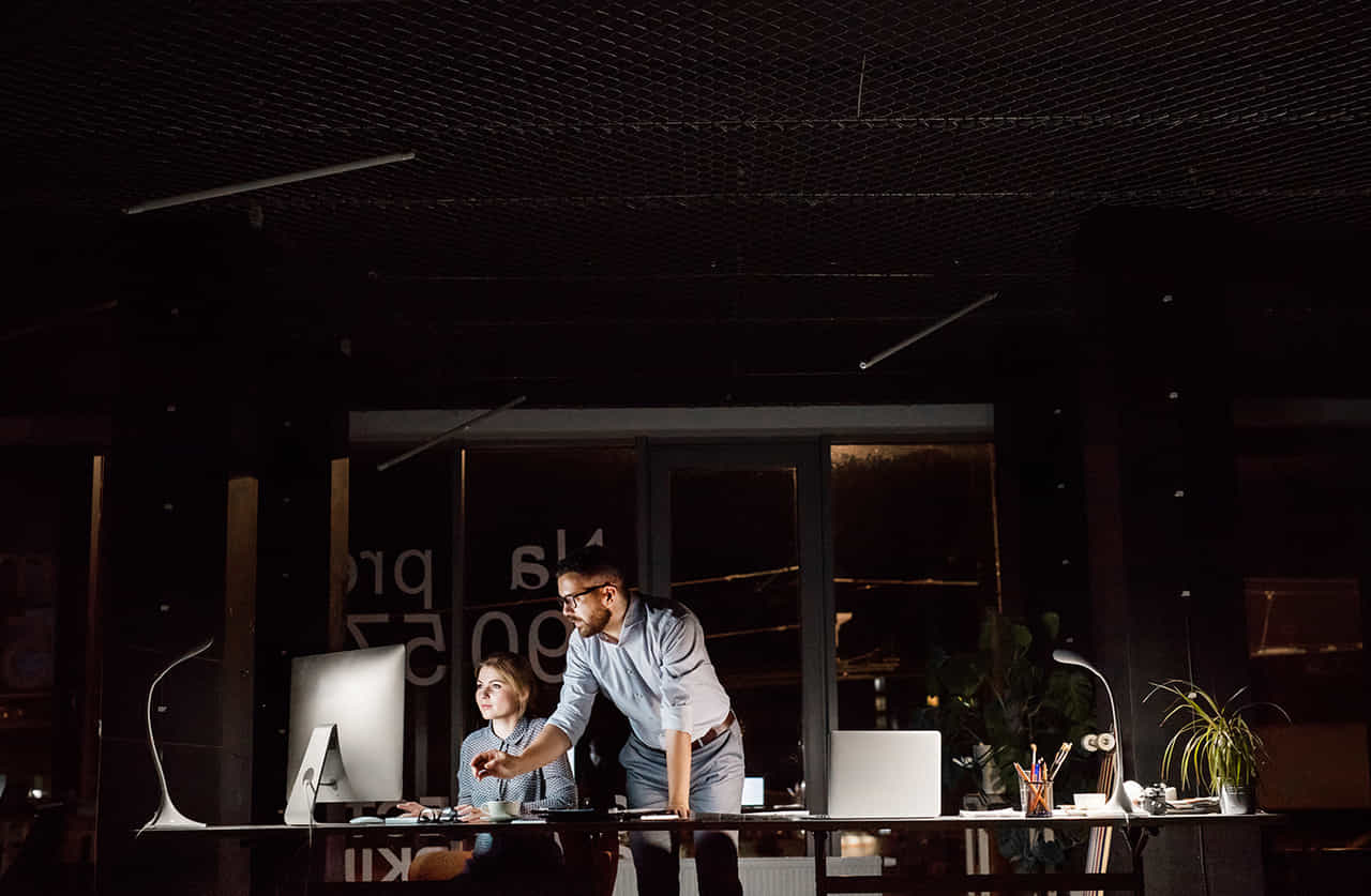 夜のオフィスで二人きりでPCで仕事をする男女