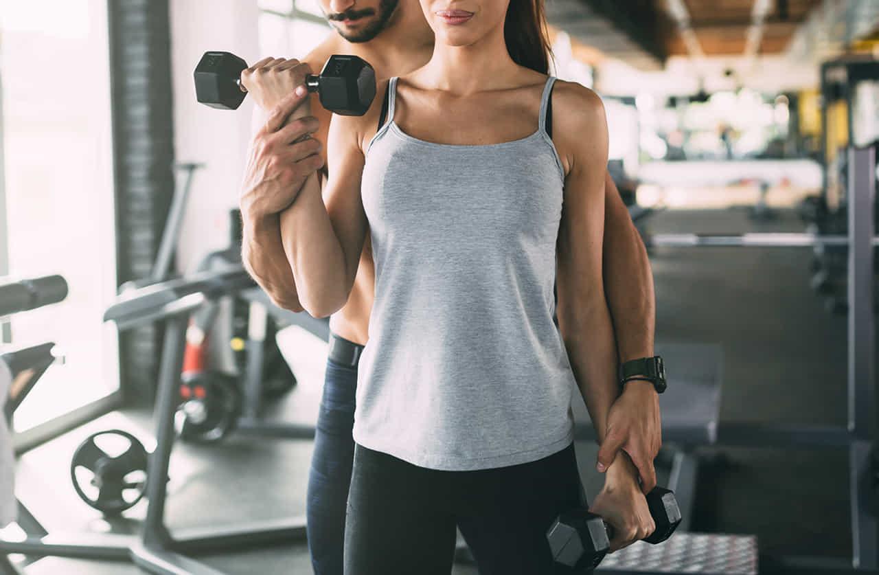 スポーツクラブでダンベルを持ってエクササイズをする女性に体に触れて指導するインストラクターの男