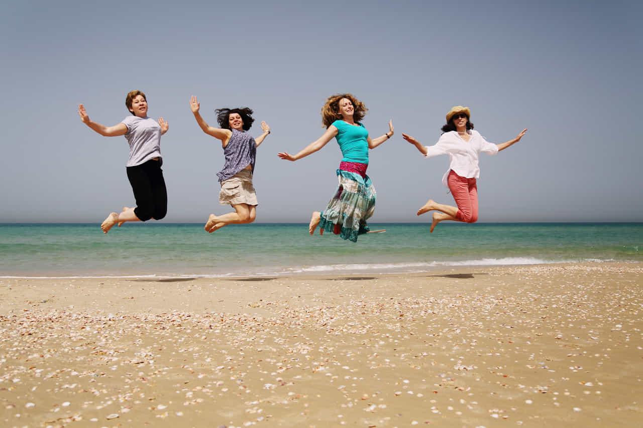 壮年の女性たち4人が浜辺でジャンプ