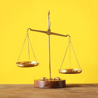 黄色いバックあるテーブルの上のアンティークの天秤