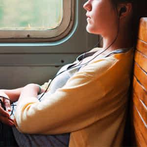 窓際に座り、イヤホンで音楽を聞く、憂いの表情をした女性