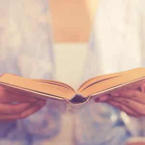 両手で開いた本を持っている女性の手元