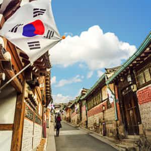 晴れやかな空に国旗がはためく韓国の昔ながらの町並み