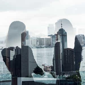 ウォーターフロントのビルを眺めながら会話する二人の女性社員