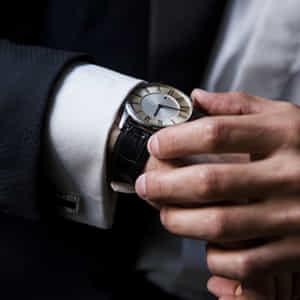 高級上時計で時間を確認するスーツの男の手のクローズアップ